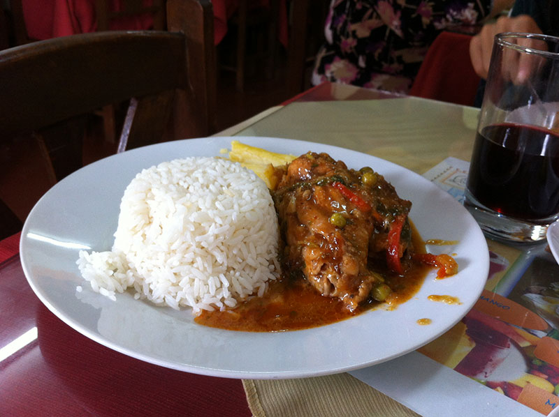 A cheap menu del dia of a really tasty stewed chicken dish with chica morada on the side